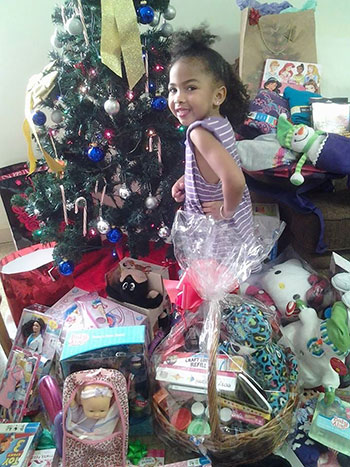 """Cadence Thomas poses next to her first-ever Christmas tree at The Children's Home in December 2013. """"It was my daughter's first real Christmas,"""" said her mother, Candice."""